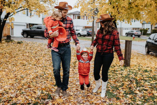 A family with two children dressed as firefighters for Halloween walk through a leaf strewn park.