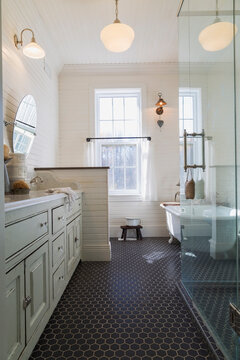 Bathroom with black tiled floor, cream paneled walls and sash windows. Stand alone white bath and glass shower cubicle.