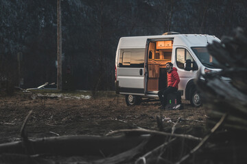 A man sitting outside his campervan in the evening with the forest in the background.