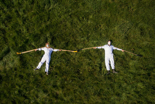 High angle view of two people wearing hazmat suits lying on a lawn during Corona virus crisis, demonstrating social distancing with wooden sticks.