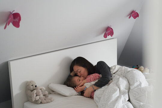 Home life, a school morning during lockdown. Mother and daughter in bed having a lie in.