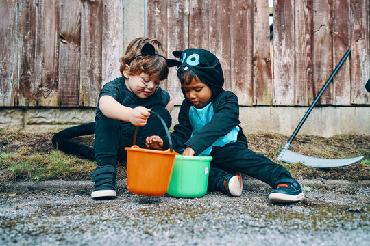 Two children dressed for Halloween sitting at the side of the road looking into their buckets of sweets.