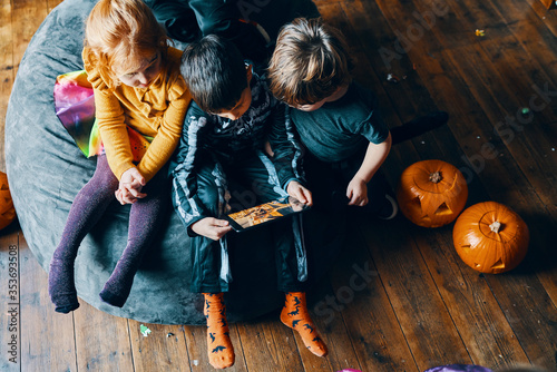 Three children sitting on a beanbag looking at a computer tablet.
