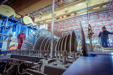 Engineers inspecting a turbine in a  nuclear power station.