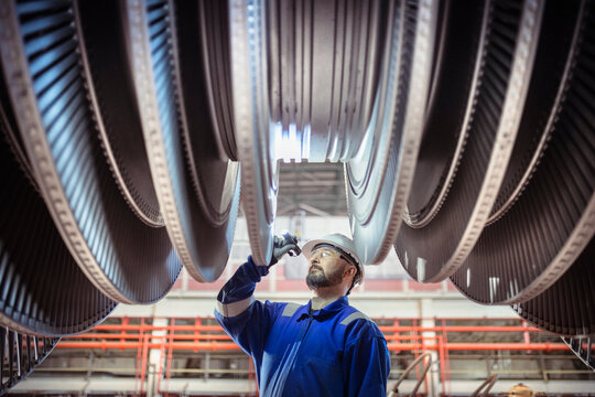 Engineer inspecting turbine in nuclear power station