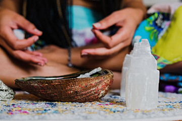 Woman burning sage to promote health, clarity and healing at home for relaxation