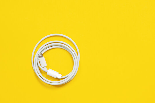 May 01, 2020, Rostov, Russia: White Apple wire lightning to usb type c, arranged in round skein on bright yellow background.