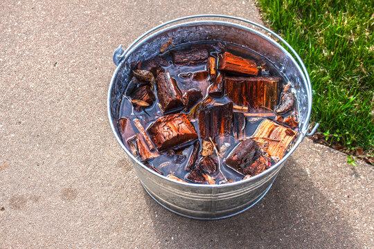Chunk wood to use in food smoker soaking in water in a tin bucket sitting on sidewalk