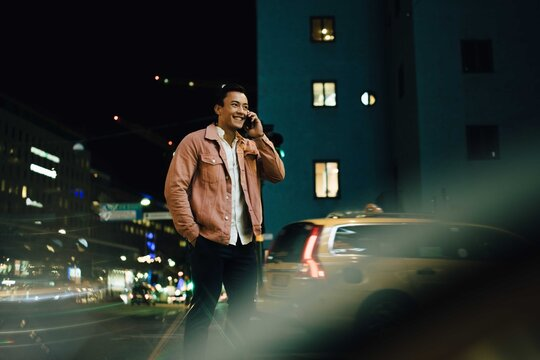 Smiling man talking through smart phone while standing in illuminated city at night