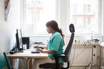 Side view of mature female doctor working over computer while sitting in clinic