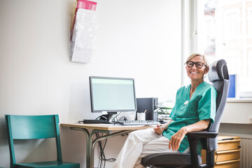 Portrait of smiling mature female doctor sitting on chair at clinic desk