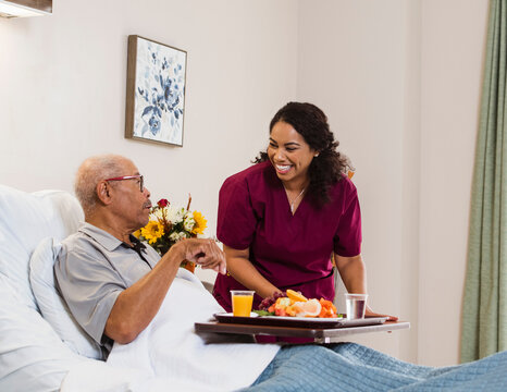 Smiling nurse hanging food to senior man in bed