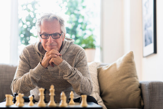 Senior man sitting in living room and playing chess