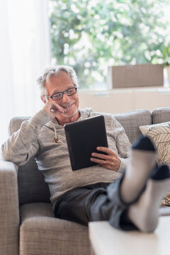 Senior man sitting on couch in living room, using tablet pc and smiling