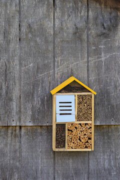 bug hotel on the side of a weathered barn for atracting mason bees and other insects that polinate but would otherwise damage wood structures on your property