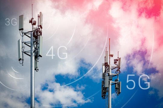 Two telecommunication towers with 4G, 5G transmitters. Cellular base stations with transmitting antennas on a telecommunication tower on a background of blue sky with pink-yellow clouds.