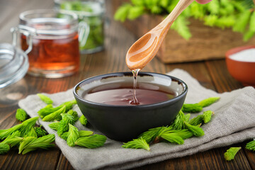 Cooked syrup or honey from spruce tips in a black bowl, jar of  jam or honey from fir buds and needles, twigs of fir tree on wooden table. Making spruce tips jam at home. Papier Peint