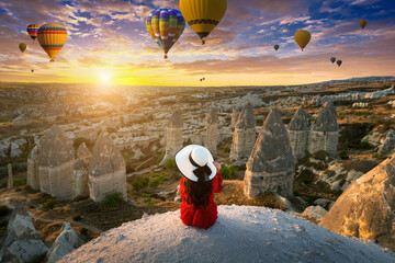 Wall Mural - Woman sitting and looking to hot air balloons at sunrise in Cappadocia, Turkey.