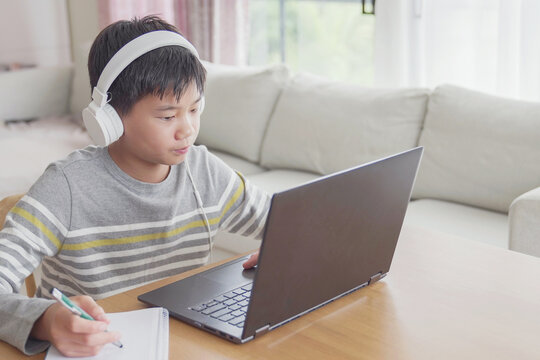 Preteen tween teen boy making facetime video calling with laptop at home, using zoom online class meeting app, social distancing,homeschooling,learning remotely , new normal concept