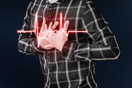 An adult man uses his hand to hold his chest. After having a heart attack symptom.