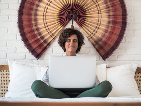 happy smiling relaxed woman in bed with laptop in Pajamas at her bedroom in home office