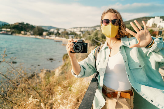 Cool beautiful happy girl woman traveler by the sea with a mask on her face, stylish outfit, with a camera in her hands, emotional expressive gestures