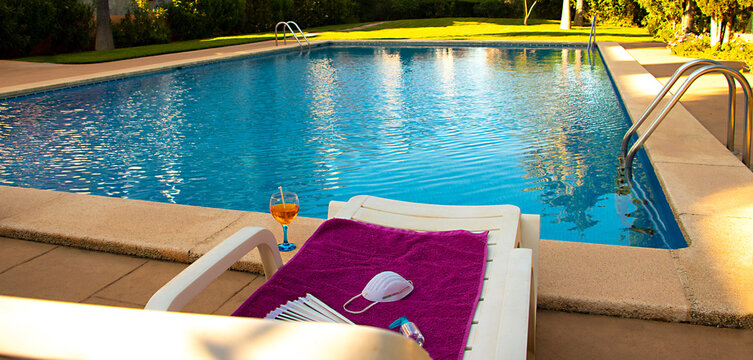 Deck chair with towel, protective mask, antiseptic, fan and coctail near the pool. Concept of Coronavirus outbreak impact on a travel industry for summer 2020.