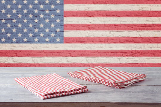 Empty wooden table with striped tablecloth over brick wall with american flag. 4th of july USA independence day mock up for design.