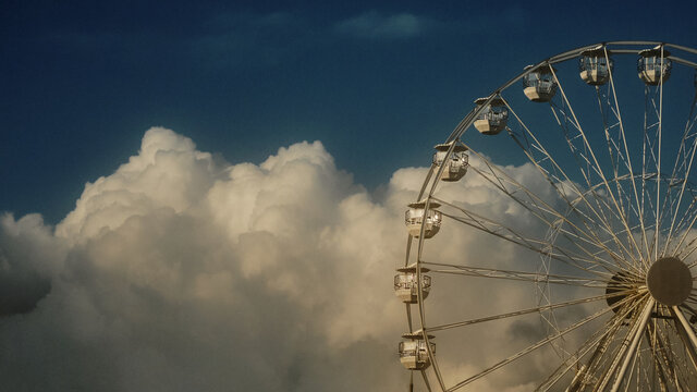 ferris wheel against blue sky and clouds