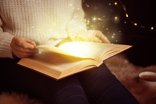 Woman reading shiny magic book, closeup view