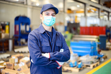 Portrait of a worker in an industrial plant wearing a mask, coronavirus concept
