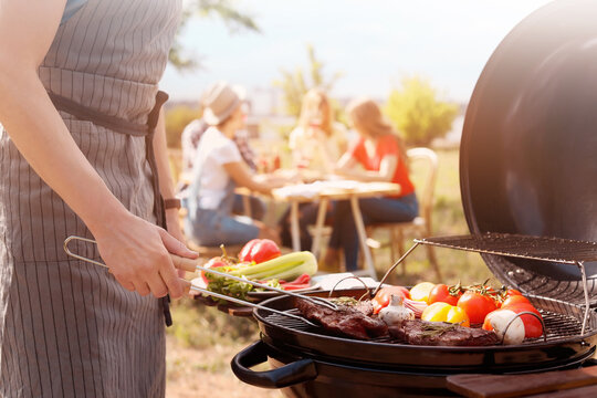 Man cooking meat and vegetables on barbecue grill outdoors, closeup