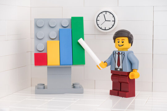 Tambov, Russian Federation - May 29, 2020 Lego minifigure businessman pointing out company growth on a chart.