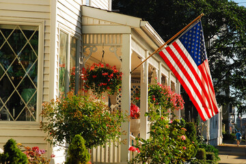 Obraz An American flag waves on the front of a home decorated with a small garden - fototapety do salonu