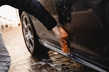 Fototapeta myjnia, mycie samochodu, mężczyzna myje swój samochód obraz