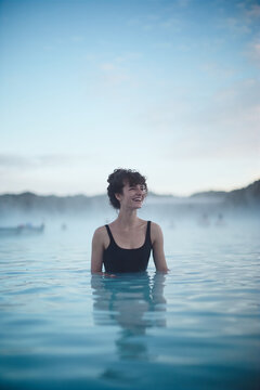 Geothermal spa. Woman relaxing in hot spring pool Blue Lagoon, Iceland