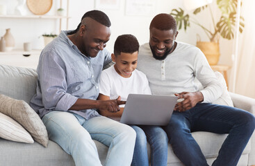 Happy African Granddad, Father And Preteen Son Using Laptop At Home Together