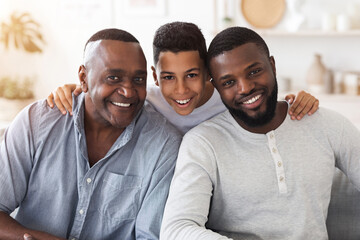 Joyful african son, dad and grandfather posing for family picture at home