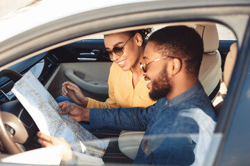 Spouses Looking At Map Sitting In Car Traveling On Vacation