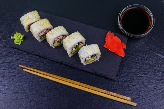 Uramaki sushi rolls with surimi on a black slate