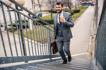 Young handsome bearded businessman climbing the stairs and going to work while holding morning coffee.