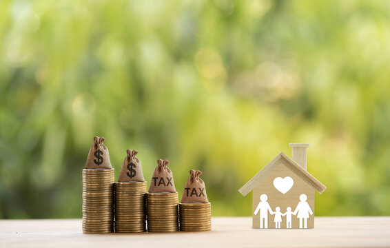 House wood with family members, dollar money bags on rows of rising coins. Concept family tax benefit, residential property or estate tax depicts home equity loan, basic needs for living