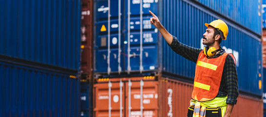 Panoramic smart creative foreman engineer man control loading containers box from cargo freight ship for import export. Logistic, transportation, import and export concept with copy space.