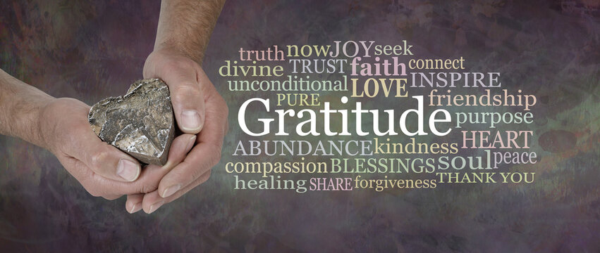 Gratitude from the Heart Word Cloud - male hands gently cupped around a wooden heart beside a  GRATITUDE word tag cloud against a wide rustic dark grunge background