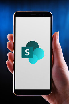 Hands holding smartphone displaying logo of SharePoint