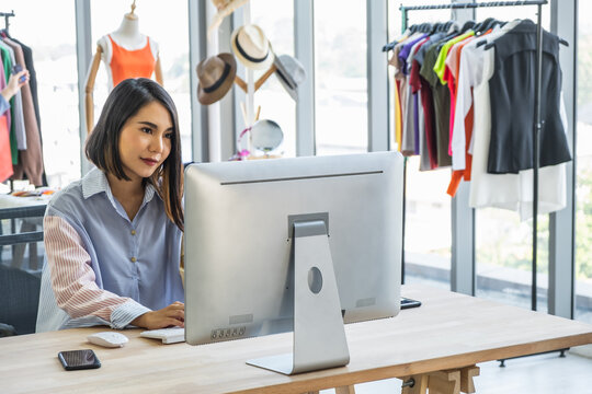 Young Asian woman business owner sitting at a desk in a clothing fashion shop working on a computer.