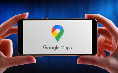 Hands holding smartphone displaying logo of Google Maps