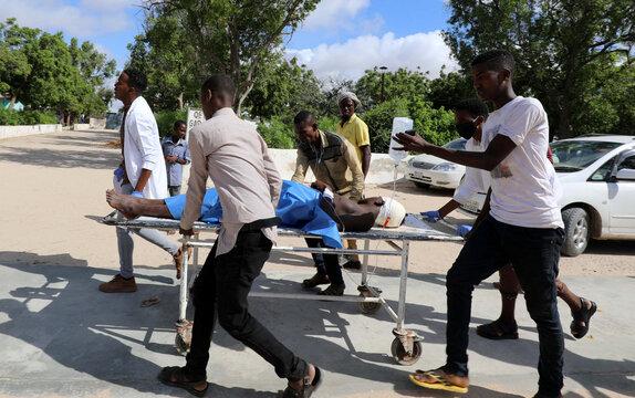 Civilians at Madina hospital assist an injured man after a minibus struck a roadside bomb at Hawa Abdi village, northwest of Mogadishu