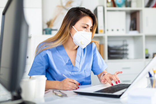 Female doctor in face mask working on laptop