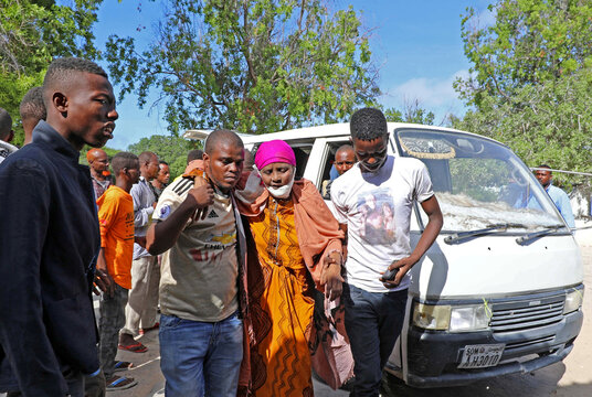 Civilians at Madina hospital assist an injured woman after a minibus struck a roadside bomb at Hawa Abdi village, northwest of Mogadishu
